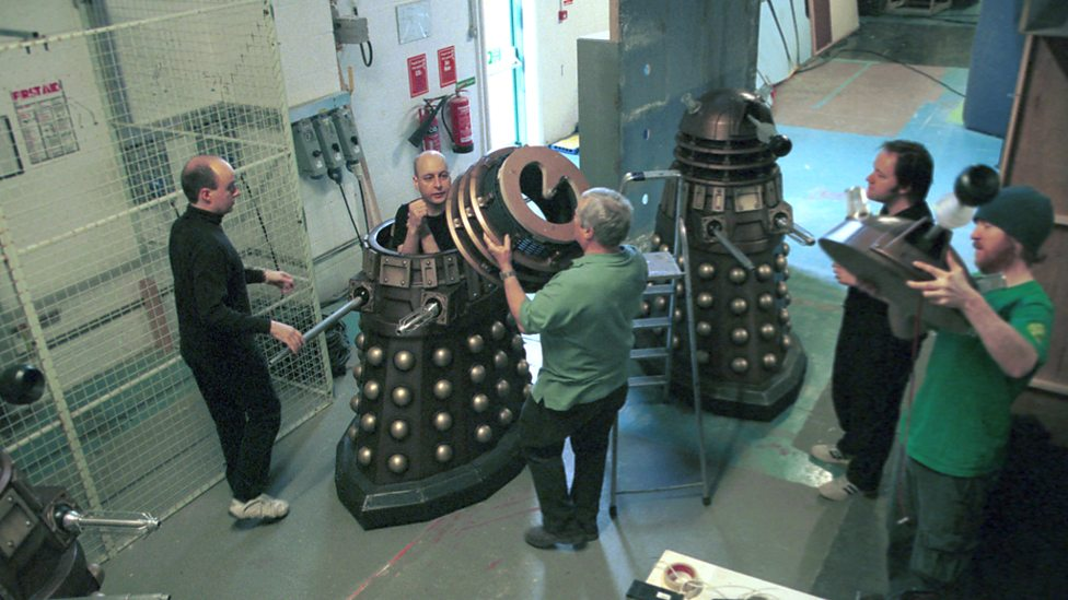 Barnaby Edwards (left) watches as Nicholas Pegg is helped into his Dalek